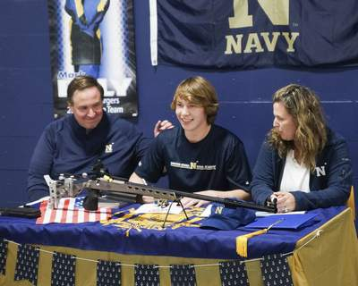 Mike Moore | The Journal Gazette Mark Dely, center, signs a commitment letter to the U.S. Naval Academy at The X Count on Wednesday.