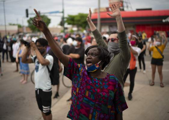 Demonstrators chant at police officers outside the Minneapolis police 3rd Precinct in Minneapolis on Wednesday afternoon, May 27, 2020. The mayor of Minneapolis called Wednesday for criminal charges against the white police officer seen on video kneeling against the neck of Floyd George, a handcuffed black man who complained that he could not breathe and died in police custody. (Jeff Wheeler/Star Tribune via AP)