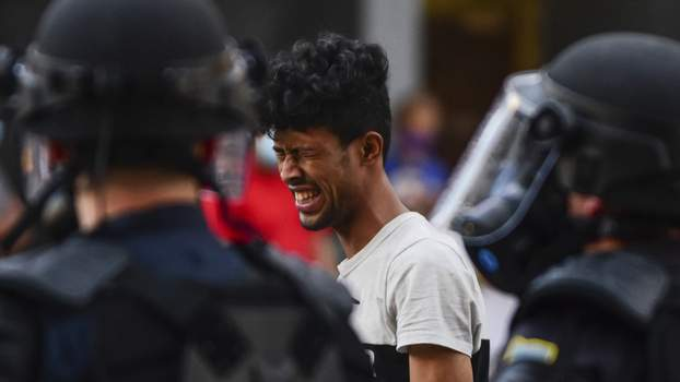 A protester reacts to being hit in the face with pepper spray Friday  in downtown Fort Wayne. (The_Journal_Gazette)