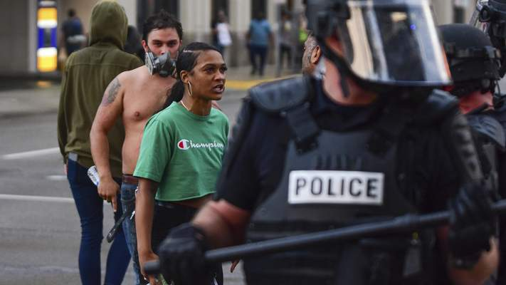 Mike Moore | The Journal Gazette  Emotions erupt outside the courthouse on Friday as protestors face off with riot police in downtown Fort Wayne.