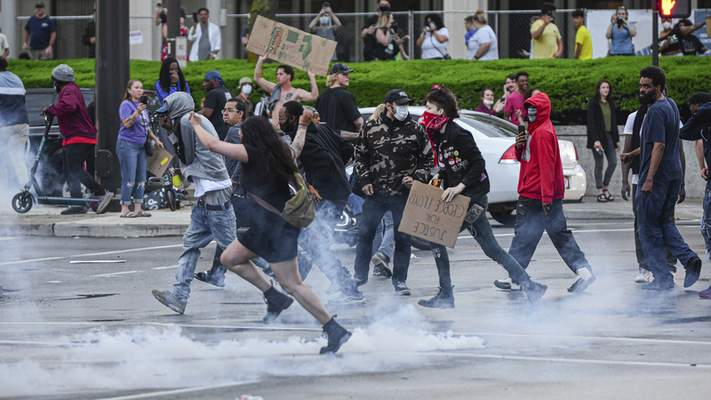 Mike Moore | The Journal Gazette Protesters run away from tear gas canisters Friday that were shot into the crowd by riot police.
