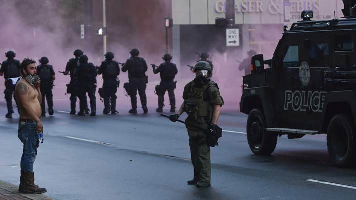 Mike Moore | The Journal Gazette  Protestors stand off against riot police on Friday as protests erupt in the streets of downtown Fort Wayne.