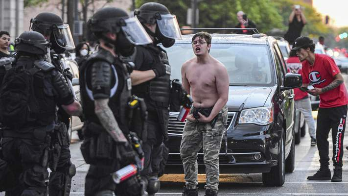 Mike Moore | The Journal Gazette  Protesters clash with riot police on Friday in downtown Fort Wayne.