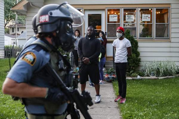 Protestors watch as police in riot gear walk down a residential street, Thursday, May 28, 2020, in St. Paul, Minn. Protests over the death of George Floyd, a black man who died in police custody Monday, broke out in Minneapolis for a third straight night. (AP Photo/John Minchillo)