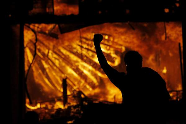 A protester gestures in front of the burning 3rd Precinct building of the Minneapolis Police Department on Thursday, May 28, 2020, in Minneapolis. Protests over the death of George Floyd, a black man who died in police custody Monday, broke out in Minneapolis for a third straight night. (AP Photo/Julio Cortez)