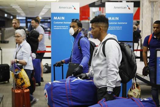 Virus Outbreak Minor League Uncertainty FILE - In this March 15, 2020, file photo, Toronto Blue Jays minor league baseball player Jesus Navarro, left center, wears a mask while he prepares to fly home along with his teammates from the Dominican Republic at Tampa International Airport in Tampa, Fla. Unlike the NFL, NBA or Major League Baseball that can run on television revenue, it's impossible for some minor sports leagues in North America to go on in empty stadiums and arenas in light of the coronavirus pandemic. These attendance-driven leagues might not play again at all in 2020, putting some teams in danger of surviving at all and potentially changing the landscape of minor league sports in the future. (Octavio Jones/Tampa Bay Times via AP, File) (Octavio Jones