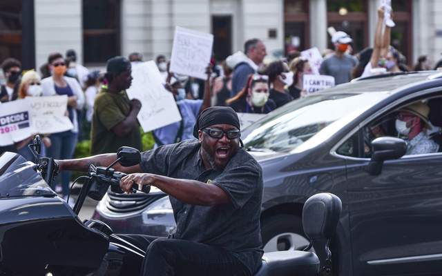 Mike Moore | The Journal Gazette Emotions run high outside the courthouse on Friday as a motorist shouts out in support of protestors as they chant and hold up signs condemning the death of George Floyd.