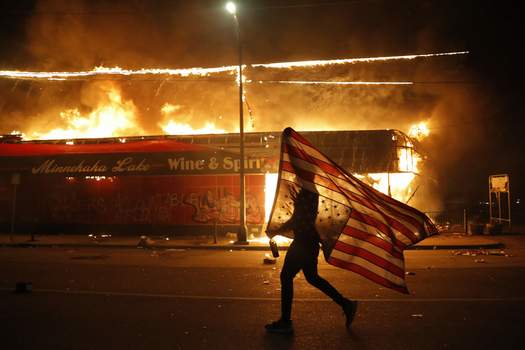 APTOPIX Minneapolis Police Death Associated Press photos A protester carries a U.S. flag upside down, a sign of distress, next to a burning building late Thursday in Minneapolis. (Julio CortezSTF)