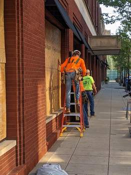 Cleanup Dave Gong | The Journal Gazette: Windows were being or have been boarded up on several downtown Fort Wayne businesses Saturday morning, mainly at the intersections of Wayne and Berry streets and Wayne and Calhoun streets. Teams of people, armed with brooms and dustpans, were sweeping broken glass and other debris.