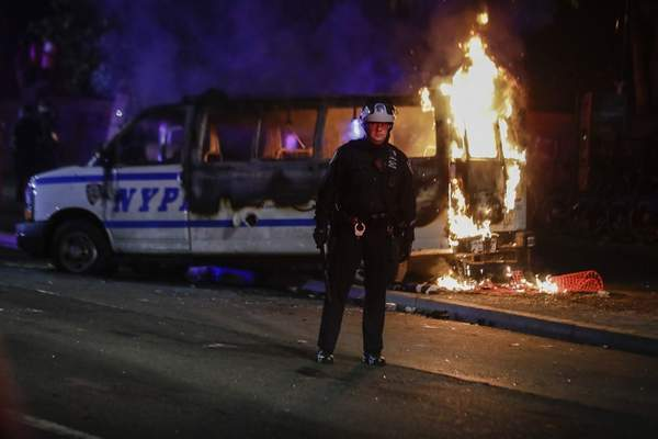 A police officer watches a crowd as a police vehicle burns near Fort Greene Park in the Brooklyn borough of New York after protesters rallied outside Barclays Center over the death of George Floyd, a black man who died Memorial Day while in police custody in Minneapolis, Friday, May 29, 2020. (AP Photo/Frank Franklin II)