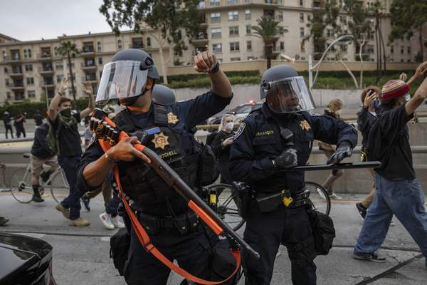 Police officers hold their position as protesters march by in Los Angeles, Friday, May 29, 2020, in protest over the death of George Floyd, who died in police custody on Memorial Day in Minneapolis. (AP Photo/Christian Monterrosa)