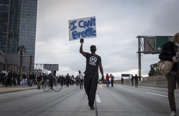 Demonstrators march in Los Angeles, Friday, May 29, 2020, in protest over the death of George Floyd, who died in police custody on Memorial Day in Minneapolis. (AP Photo/Christian Monterrosa)