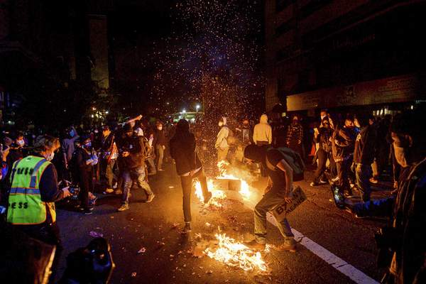 Demonstrators burn garbage in Oakland, Calif., on Friday, May 29, 2020, while protesting the Monday death of George Floyd, a handcuffed black man in police custody in Minneapolis. (AP Photo/Noah Berger)