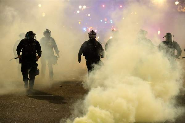Policemen walk enveloped by teargas in Portland, Friday, March 29, 2020. After hours of largely peaceful demonstrations, violence escalated late Friday in downtown Portland, as hundreds of people gathered to protest the Minneapolis police killing of a black man George Floyd.(Dave Killen/The Oregonian via AP)