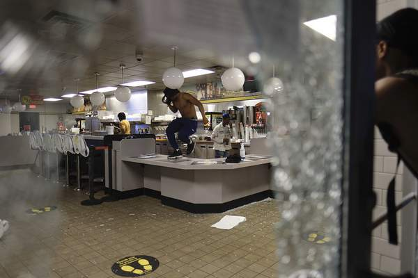 Protestors break into a Waffle House as protestors returned to the area around the Centennial Olympic Park and CNN center, early Saturday, May 30, 2020, in Atlanta, Georgia. Protests continued following the death of George Floyd, who died after being restrained by Minneapolis police officers on Memorial Day. (Be Gray/Atlanta Journal-Constitution via AP)
