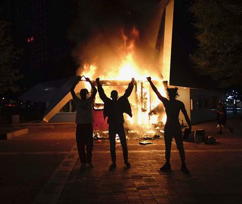 Protestors raise their hands in front of a burning vending cart outside of the visitor bureau office in Centennial Park, late Friday, May 29, 2020, in Atlanta, Georgia. Protests continued following the death of George Floyd, who died after being restrained by Minneapolis police officers on Memorial Day. (Be Gray/Atlanta Journal-Constitution via AP)