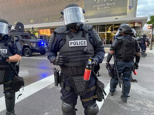 Journal Gazette Jamie Duffy  An officer in riot gear stands guard at Clinton and Berry streets, armed with a tear gas canister.