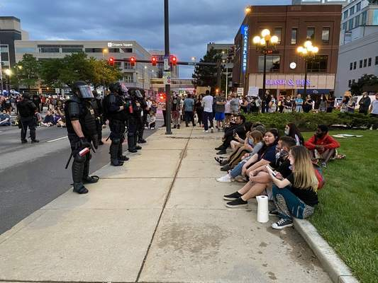 Journal Gazette Jamie Duffy    Shortly before heavy tear gas was deployed around 9:30 p.m., a line of riot police armed with tear gas canisters faced the Allen County Courthouse while a row of protesters sat down in front of them.