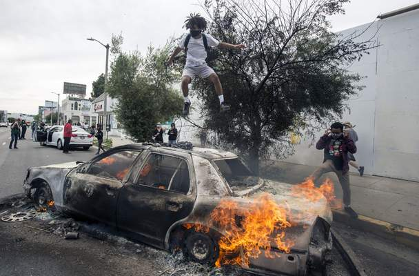 Associated Press A person jumps on a burning police vehicle in Los Angeles on Saturday during a protest over the death of George Floyd.