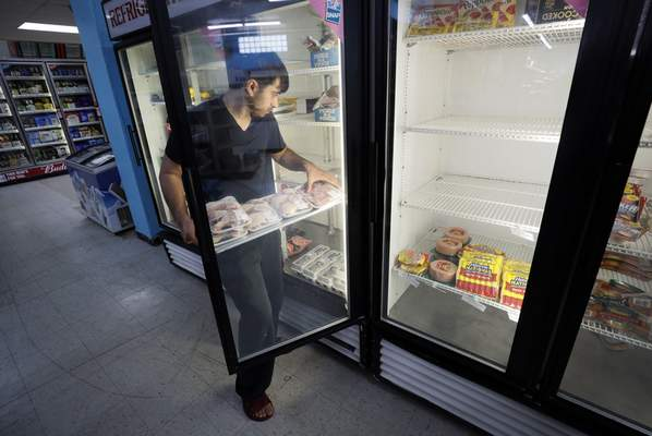 Associated Press Hardik Kalra stocks meat in a cooler Friday in Des Moines, Iowa. Experts warn that price increases at grocery stores might stick around.