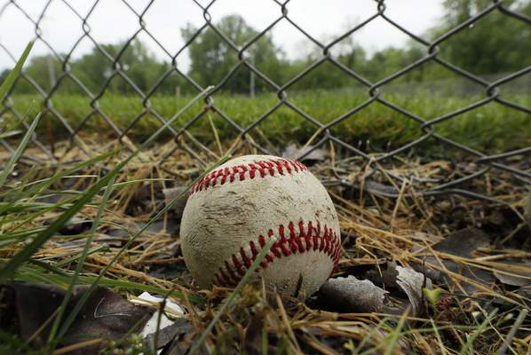 Associated Press A baseball sits in the grass last week outside a closed field at the Campbell Recreation Area in Clive, Iowa. The field has been closed for several weeks due to the coronavirus pandemic.