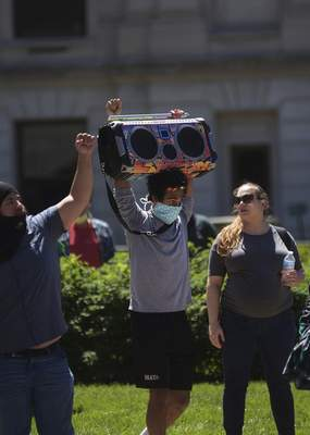Katie Fyfe | The Journal Gazette  A protester carries around a boom box to play music during the protest of thedeath of George Floyd on Sunday.