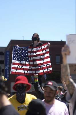 Katie Fyfe | The Journal Gazette  A protester holds an American flag with the words Black Lives Matter written on it during the protest of thedeath of George Floyd on Sunday in front of the Allen County Courthouse.