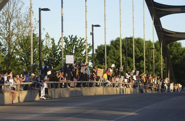 Crowds gather along Dr. Martin Luther King Jr. Memorial Bridge on Sunday afternoon. The third day of protests took on a calmer tone.