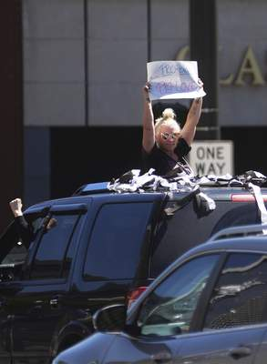 Katie Fyfe | The Journal Gazette  A protester drives past the Allen County Courthouse holding a sign reading Pro-Black, Pro-Love on Sunday.