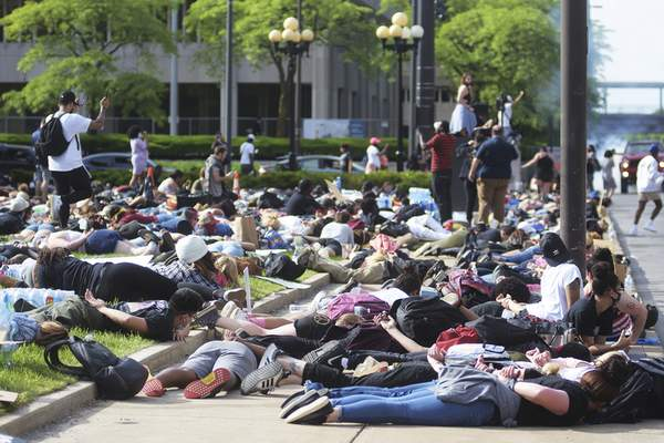 Katie Fyfe | The Journal Gazette  Protesters lay on their stomachs with their hands behind their backs duringSunday's protest in front of the Allen County Courthouse.