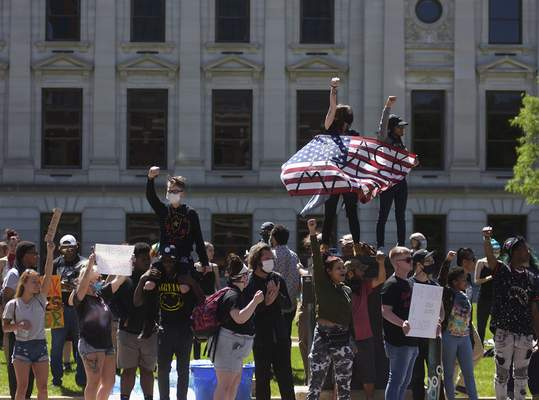Protesters throw their fists in the air as they gather in front of the Allen County Courthouse.