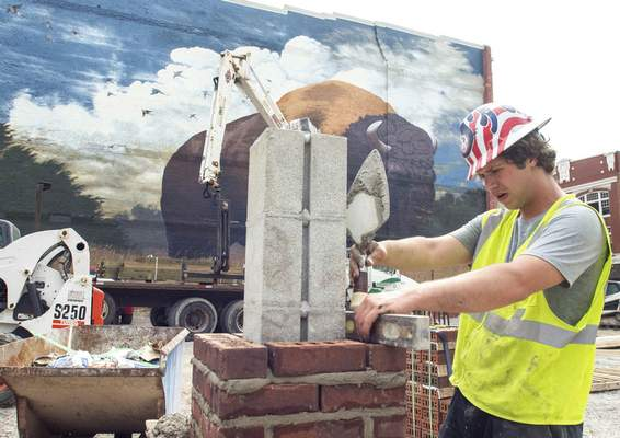 Michelle Davies | The Journal Gazette Donald Studebaker, with Fetter's Construction, uses a level as he builds a brick pier in a parking lot at the corner of West Columbia and Harrison Streets Wednesday morning.