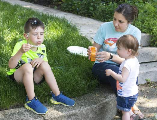 Michelle Davies | The Journal Gazette Nora Oyer, 18 months, watches as big brother Davis, 4, blows bubbles Tueday morning with babysitter Rachel Heneveld looking on.