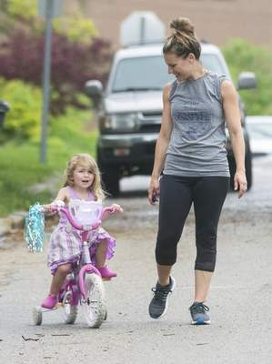 Michelle Davies | The Journal Gazette Mandy Miller escapes the house after rain showers Thursday morning with her daughter Selah, 3, as she rides her tricycle along Forest Avenue.