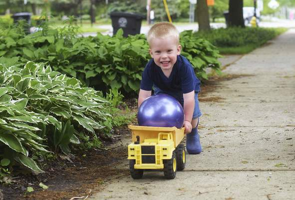 Katie Fyfe | The Journal Gazette Luke Lent, 2, pushes his dump truck with a ball in it down the sidewalk along West Foster Parkway on Friday, May 29th, 2020.