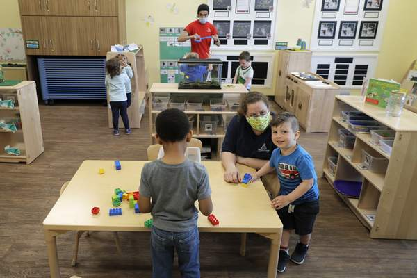 In this May 27, 2020, photo, teachers Jana Blair, right, and Aaron Rainboth, upper-center, wear masks as they work with kids at the Frederickson KinderCare daycare center, in Tacoma, Wash. (AP Photo/Ted S. Warren)