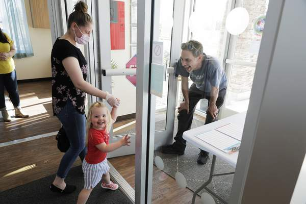 In this May 27, 2020 photo, Samantha Sulik, left, director of the Frederickson KinderCare daycare center, in Tacoma, Wash., looks on as Michael Canfield, right, waits in an entryway to pick up his daughter Aurora at the end of the day. (AP Photo/Ted S. Warren)