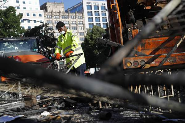 A worker cleans up burned debris on a sidewalk, Sunday, May 31, 2020, in Washington, following protests over the death of George Floyd, a black man who died in police custody in Minneapolis. (AP Photo/Patrick Semansky)