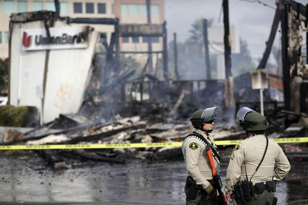 San Diego County sheriff officers stand guard in front of a burning bank building after a protest over the death of George Floyd, Sunday, May 31, 2020, in La Mesa, Calif. (AP Photo/Gregory Bull)