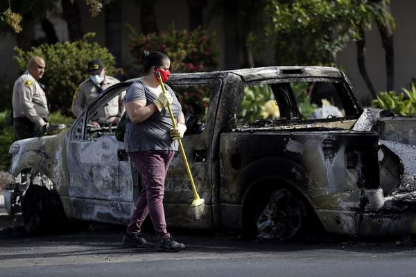A woman sweeps around a burned truck after a protest over the death of George Floyd, Sunday, May 31, 2020, in La Mesa, Calif. (AP Photo/Gregory Bull)