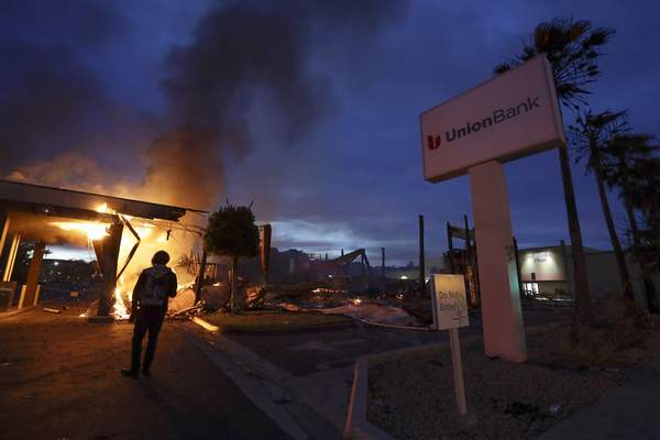 A man looks on as a bank burns after a protest over the death of George Floyd, Sunday, May 31, 2020, in La Mesa, Calif. (AP Photo/Gregory Bull)