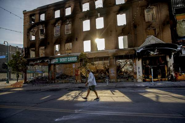 A man walks past a damaged building following overnight protests over the death of George Floyd, Sunday, May 31, 2020, in Minneapolis, Minn. (Elizabeth Flores/Star Tribune via AP)