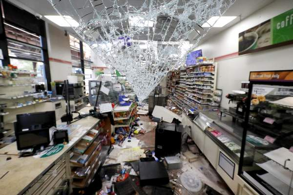 Shattered glass hangs from the doorway of a 7-Eleven store early Sunday morning, May 31, 2020 in Chicago, after a night of unrest and protests over the death of George Floyd, a black man who was in police custody in Minneapolis. (AP Photo/Charles Rex Arbogast)