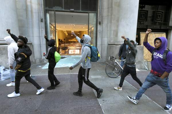 Young men play to the presence of TV crews early Sunday morning, May 31, 2020, as they pass by a shattered display window at the downtown Macy's store in Chicago, after a night of unrest and protests over the death of George Floyd, a black man who was in police custody in Minneapolis. (AP Photo/Charles Rex Arbogast)