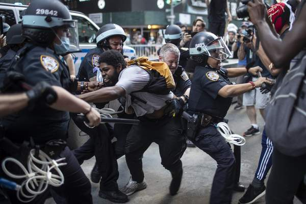 Police detain protesters as they march down the street during a solidarity rally for George Floyd, Saturday, May 30, 2020, in New York. (AP Photo/Wong Maye-E)
