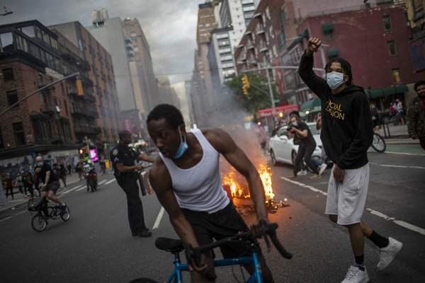 Protesters march down the street as trash burns in the background during a solidarity rally for George Floyd, Saturday, May 30, 2020, in New York. (AP Photo/Wong Maye-E)