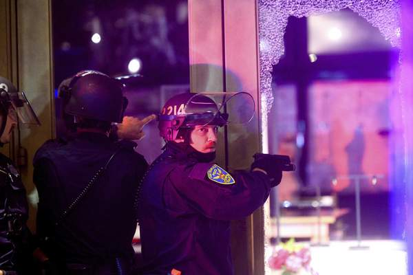 A police officer aims his weapon while clearing a vandalized Victoria's Secret store in San Francisco on Saturday, May 30, 2020. (AP Photo/Noah Berger)