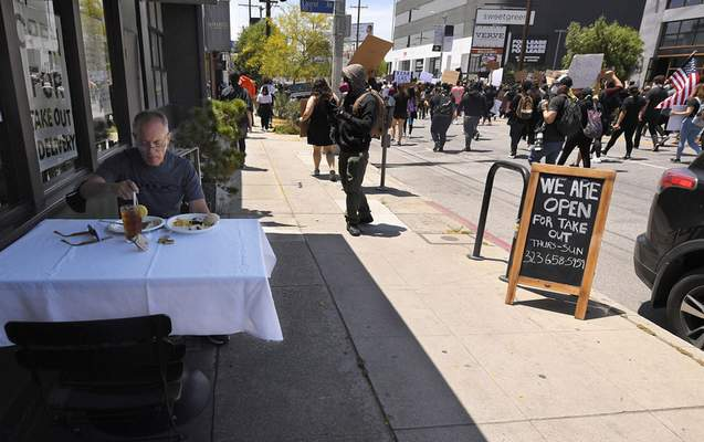 A man eats lunch as demonstrators walk along 3rd street during a protest over the death of George Floyd, Saturday, May 30, 2020, in Los Angeles. (AP Photo/Mark J. Terrill)