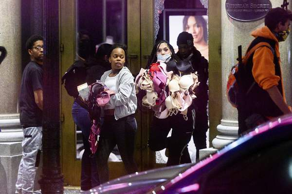 Women carry merchandise from a Union Square Victoria's Secret store in San Francisco on Saturday, May 30, 2020. (AP Photo/Noah Berger)