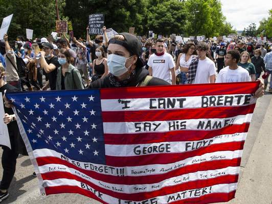 Associated Press A person holds an American flag in Eugene, Ore., on Sunday with messages on it during a Black Lives Matter march protesting the death of George Floyd.